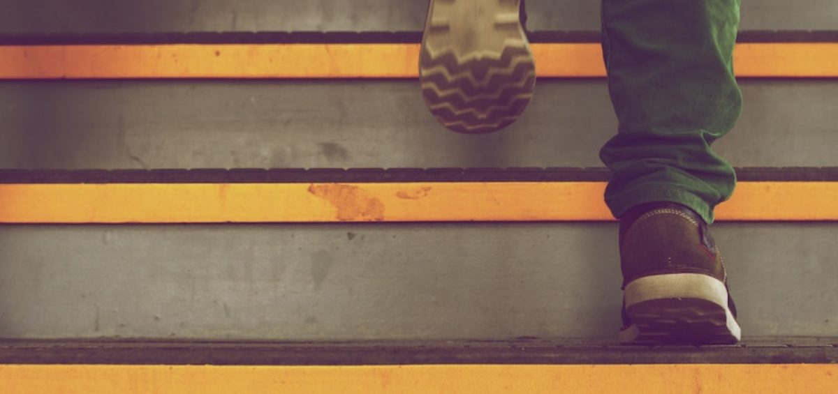 man stepping up onto a series of steps